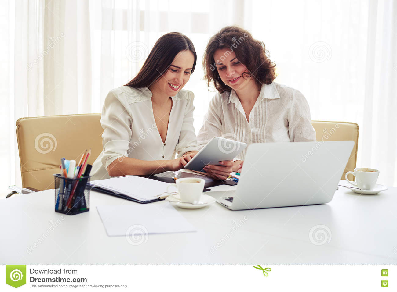 Two young women working together with gadgets in the office