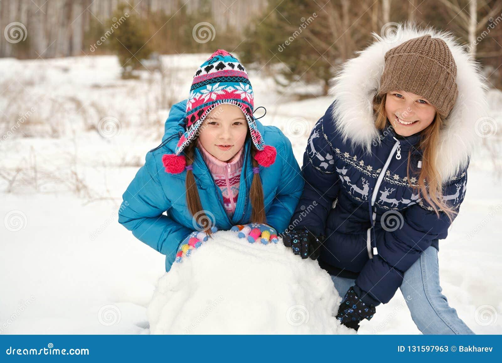 Twofunny flickor som bygger en snögubbe i vintern