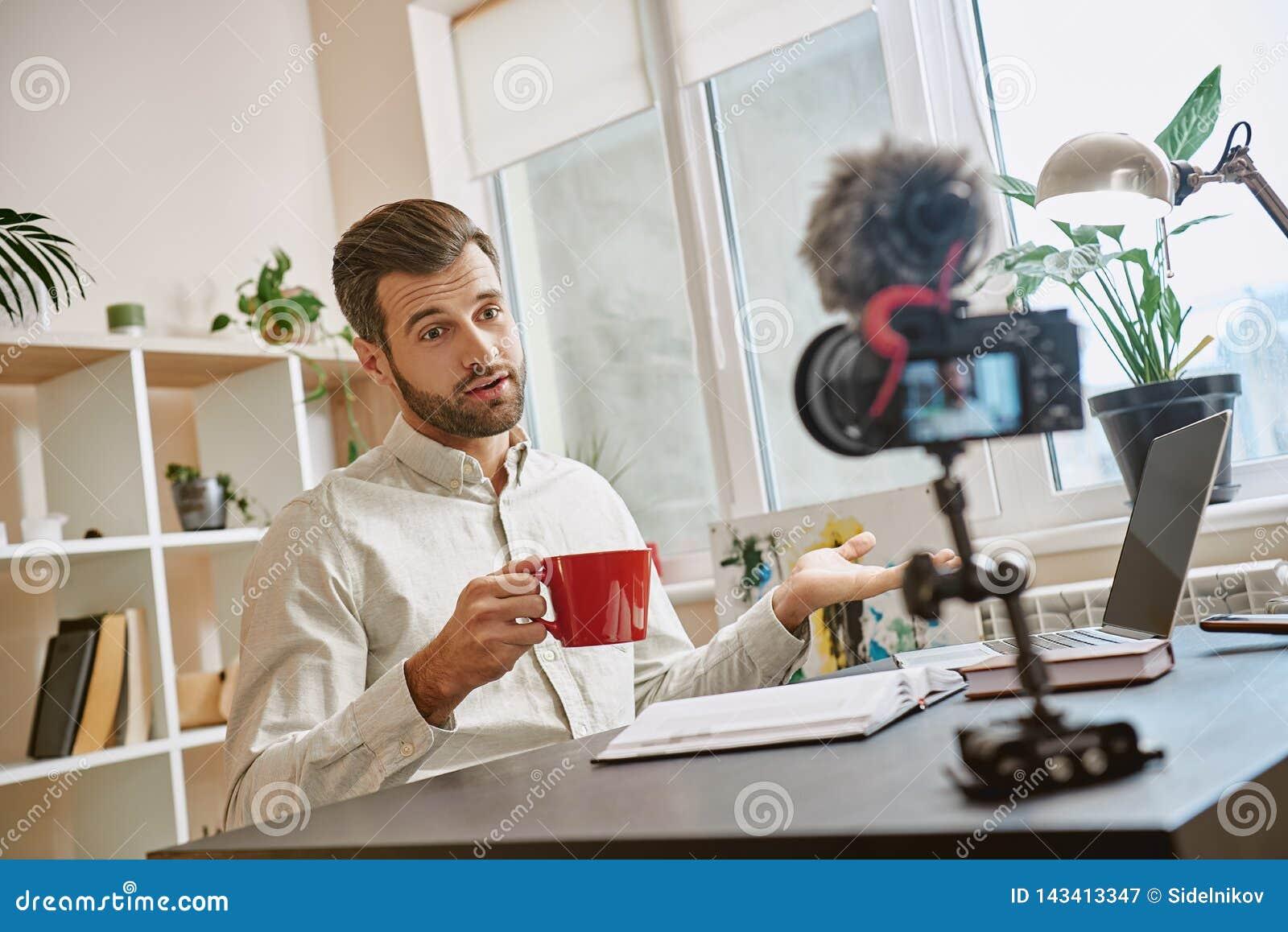Tworzyć zawartość Rozochocony męski blogger robi nowemu wideo dla jego vlog i pije herbaty podczas gdy siedzący indoors
