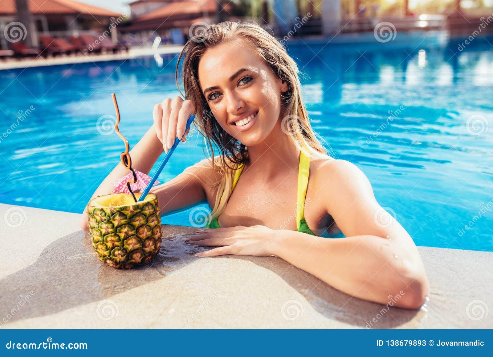 Tycka om solbrännakvinnan i bikini i simbassängen