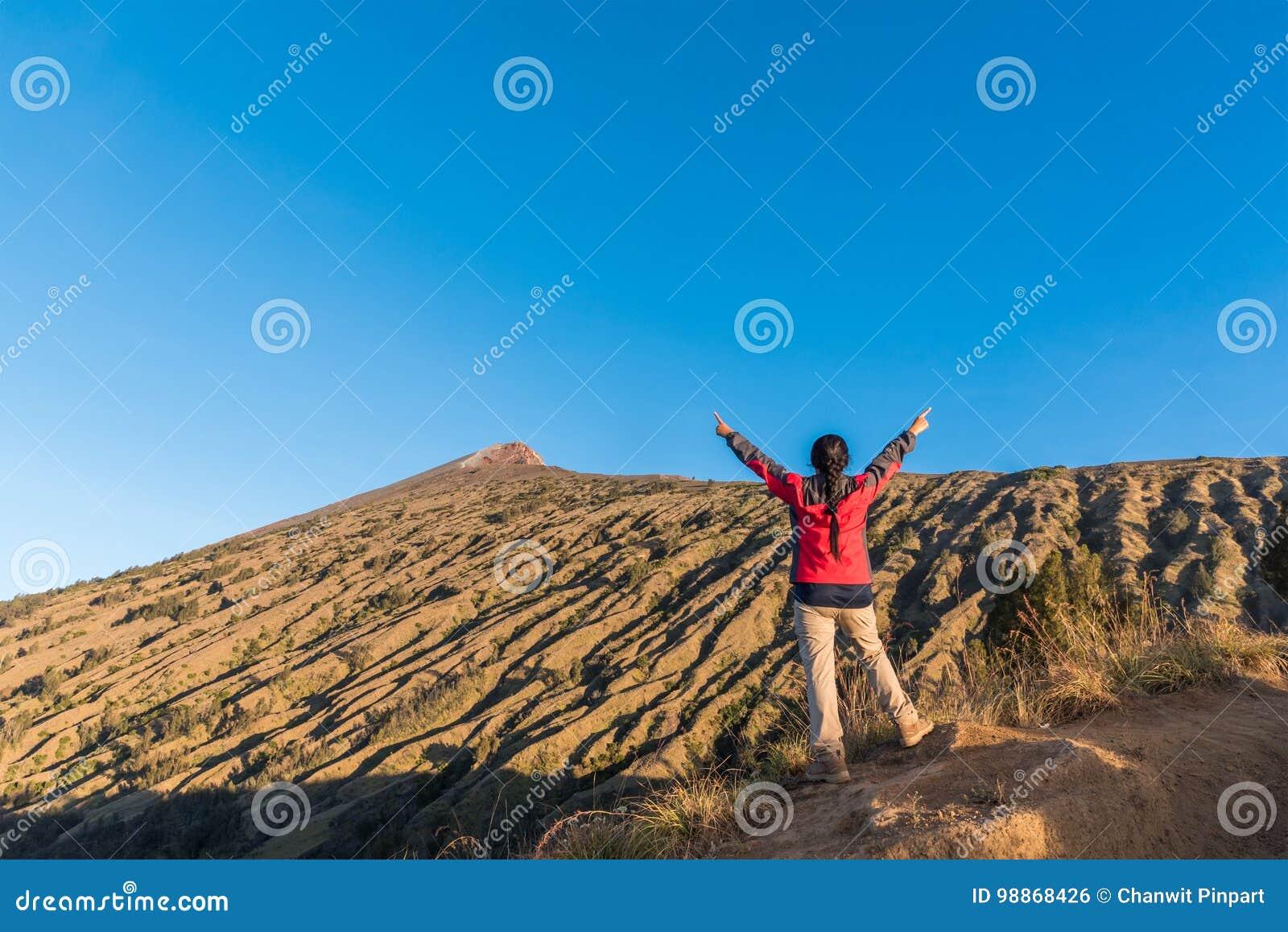 Tycker om den fördelande handen för kvinnafotvandraren, och lyckligt med bästa sikt för berg efter färdig klättring på monteringe