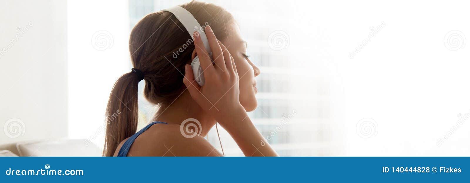 Tycker om den kvinnliga bärande hörlurar för sidosikt favorit- musik hemma