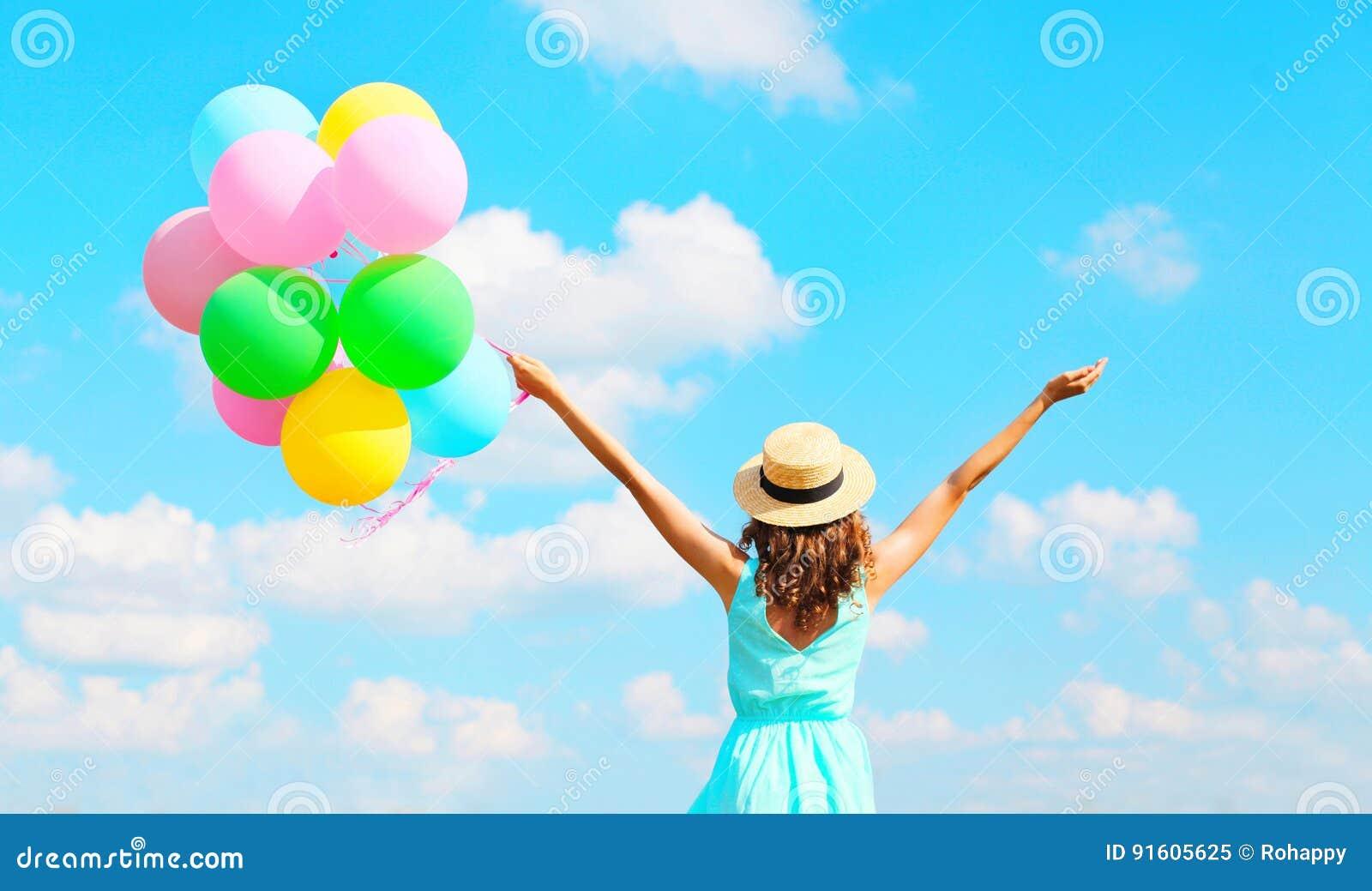Tycker om den lyckliga kvinnan för den tillbaka sikten med färgrika ballonger för en luft en sommardag på bakgrund för blå himmel