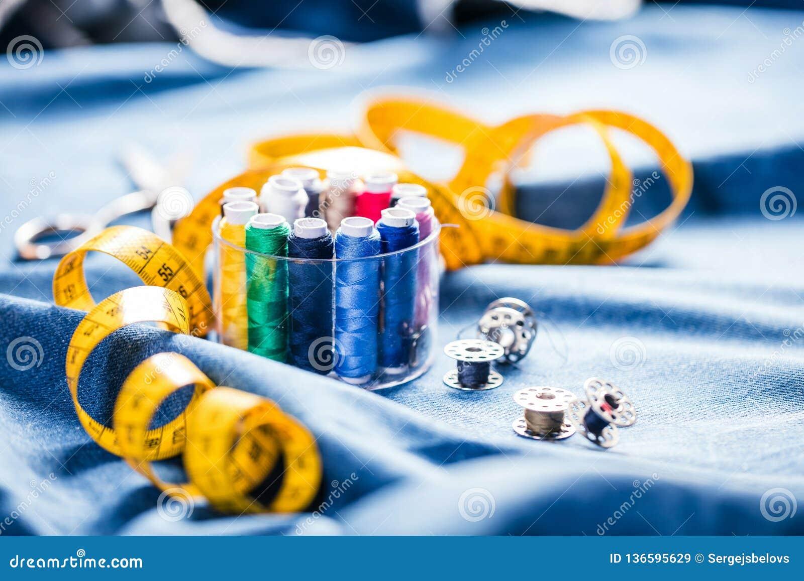 Tyg av olika typer och objekt för att sy Mångfärgat tyg, trådrullar, visare, en sömnad tafsar är nödvändigt för att sy
