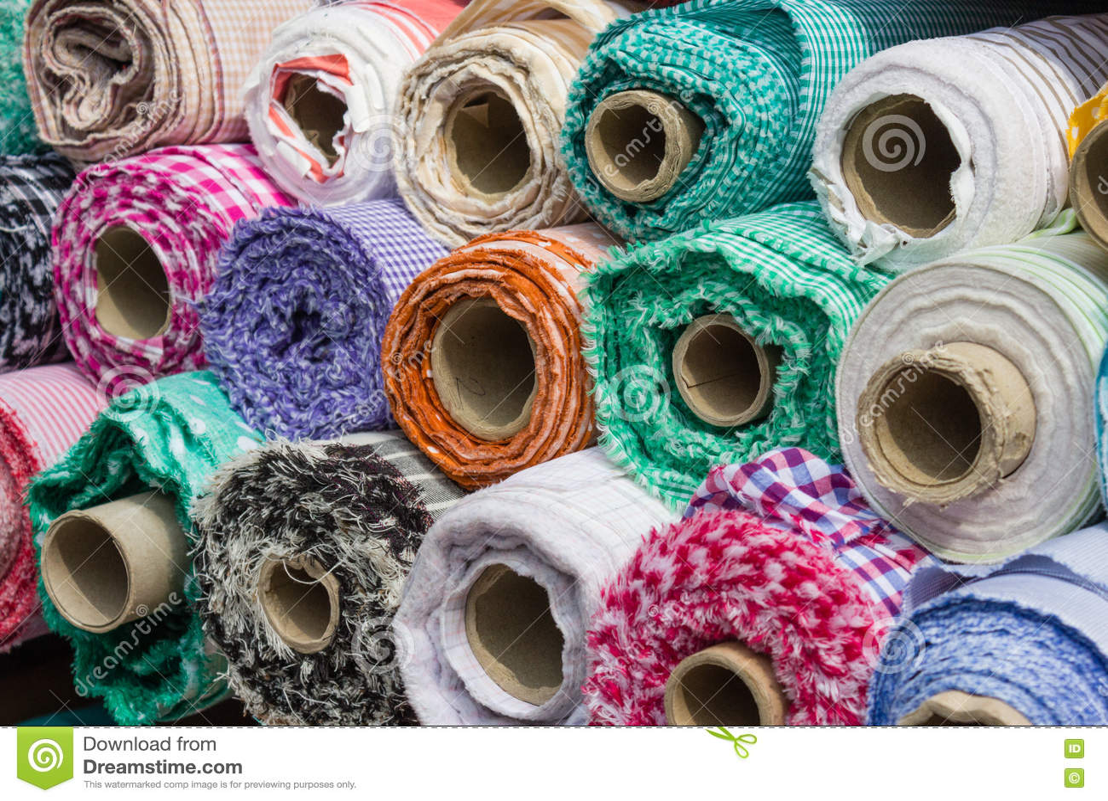 Tyg rullar på stånd, bakgrund för textilbransch