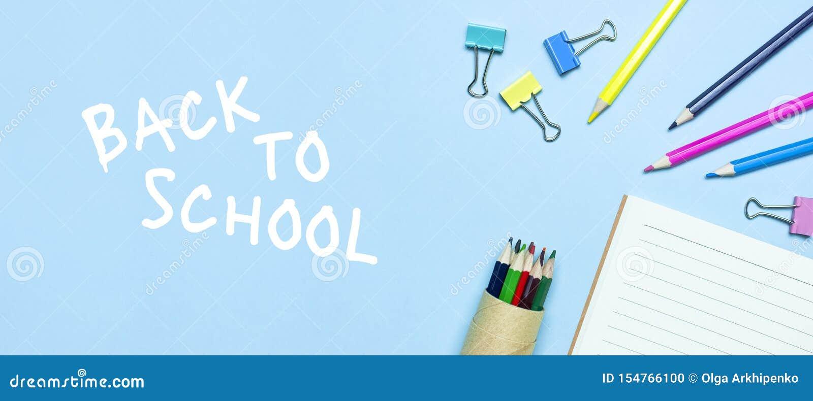 Tylna koncepcji do szko?y Drewniani barwioni ołówki, czysty szkolny notatnik w linii, papierowe klamerki na błękitnym tło odgórne