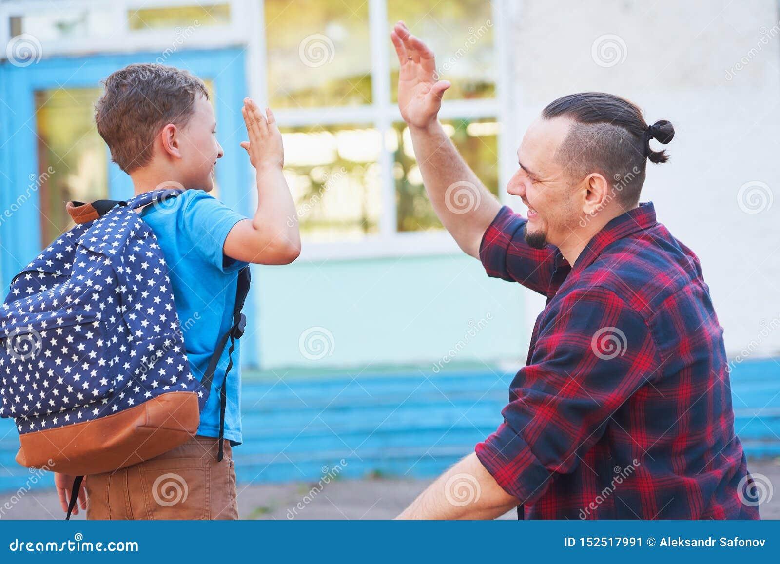 Tylna szko?y Szczęśliwy ojciec i syn jesteśmy mile widziany przed szkołą podstawową rodzic spotyka dziecka od szkoły podstawowej