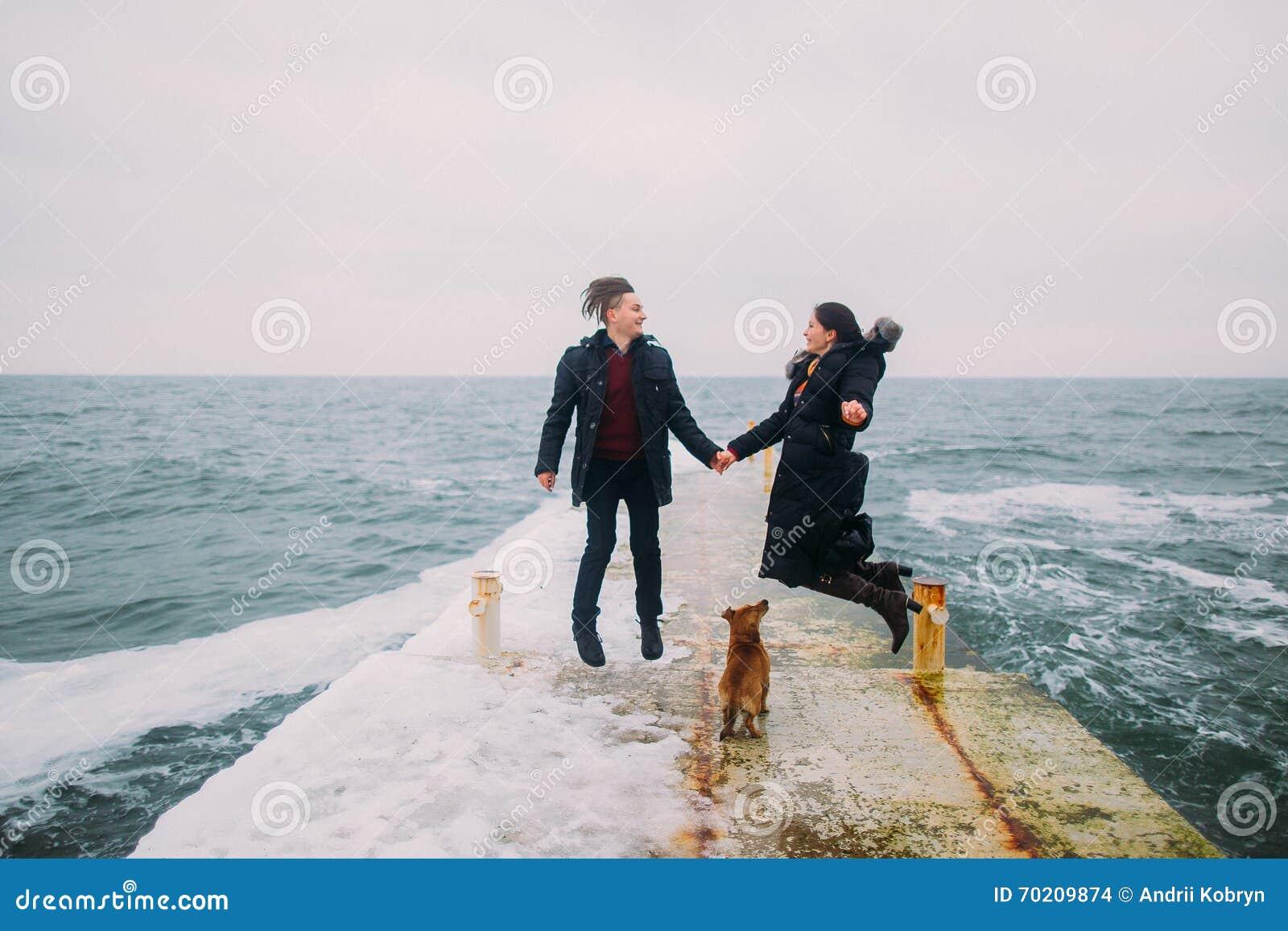 Tylni romantyczny widok młody pary odprowadzenie wraz z małego psa i mieć podczas dżdżystej jesieni zabawą na drylującym molu