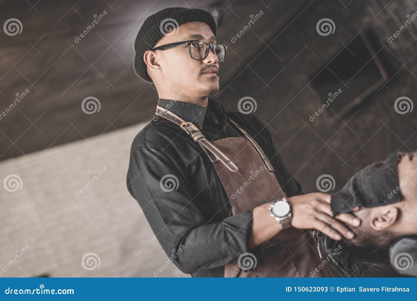 Tylni widok fryzjera męskiego mężczyzna z długie włosy robi masażem kostiumery z świeżymi ręcznikami