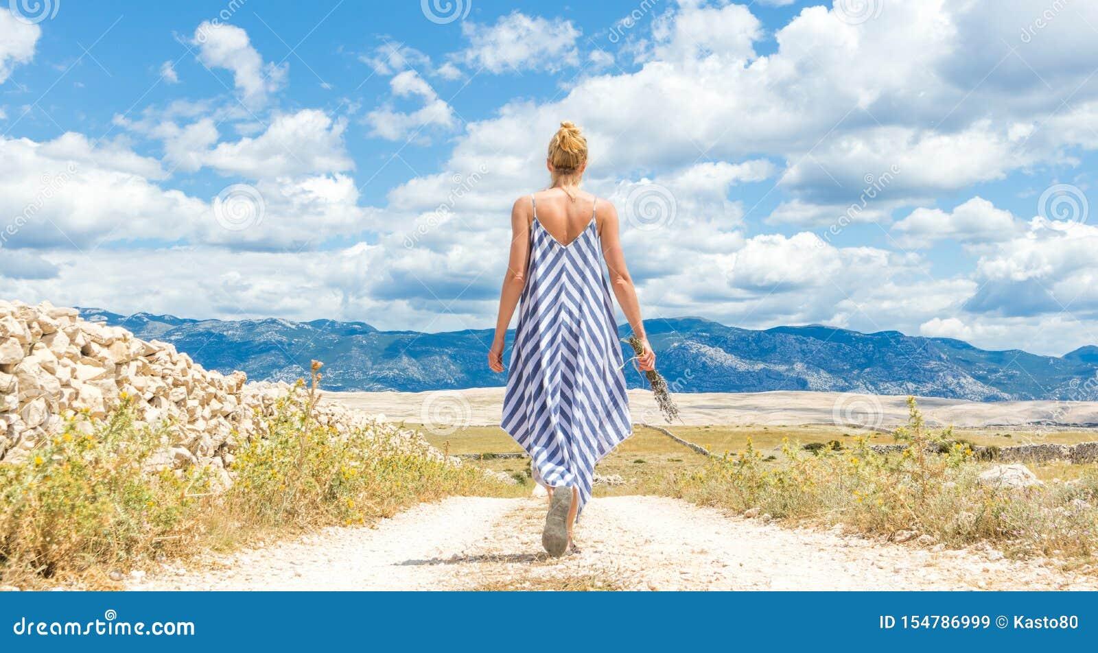 Tylni widok kobieta w lato sukni mienia bukiecie lawenda kwitnie podczas gdy chodzący plenerowy przelotowy suchy skalistego