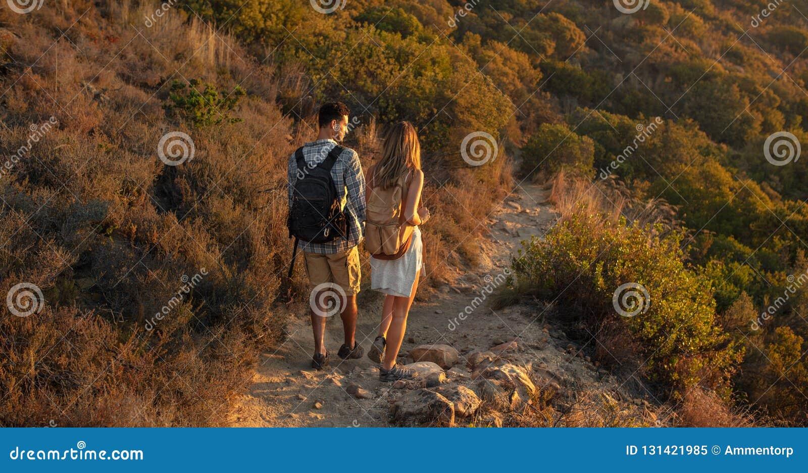 Tylni widok mężczyzny i kobiety wycieczkowicze trekking skalistą ścieżkę przy wzgórzem popiera kogoś Wycieczkowicz pary natury re