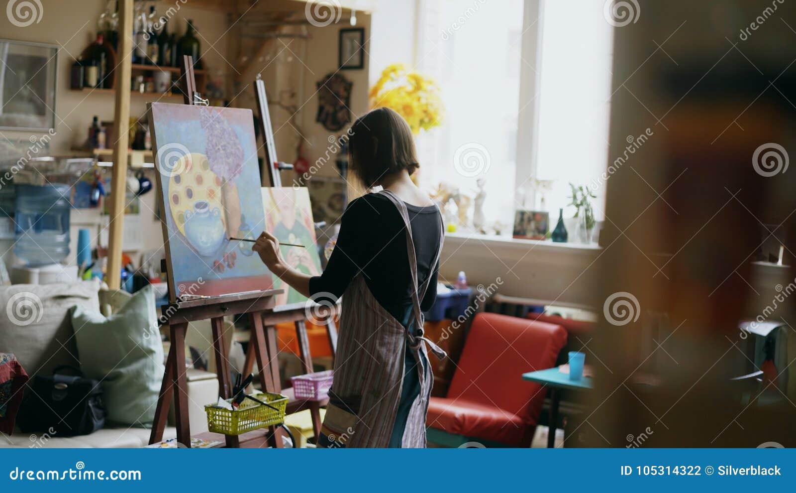 Tylni widok Młoda malarz dziewczyna maluje wciąż życie obrazek na kanwie w klasie w fartuchu