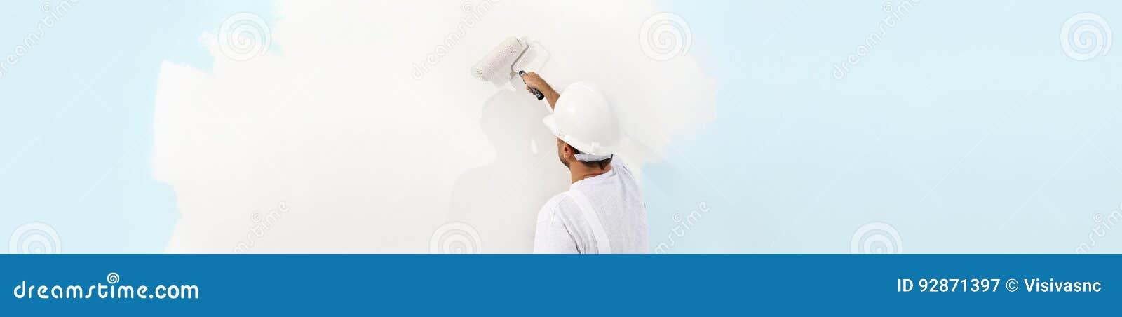 Tylni widok maluje ścianę z farba rolownikiem malarza mężczyzna, i