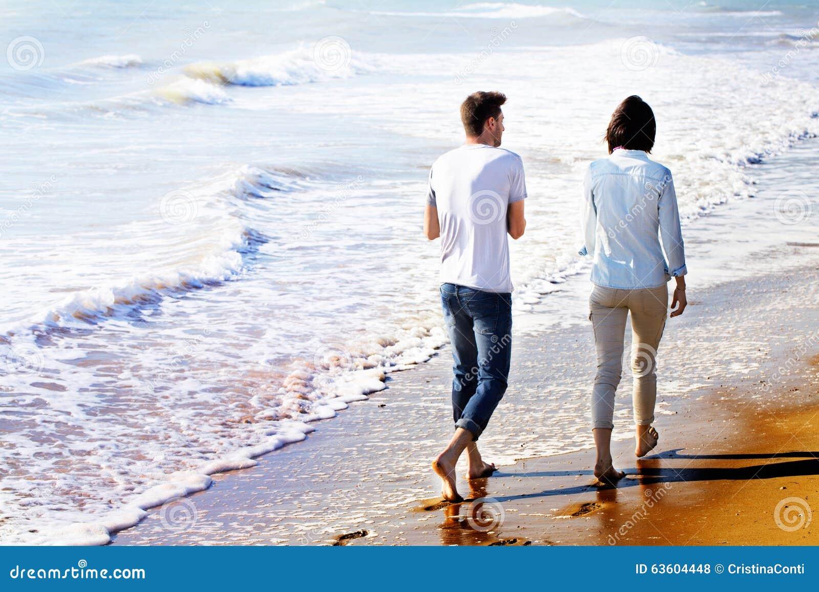Tylni widok pary odprowadzenie przy plażą
