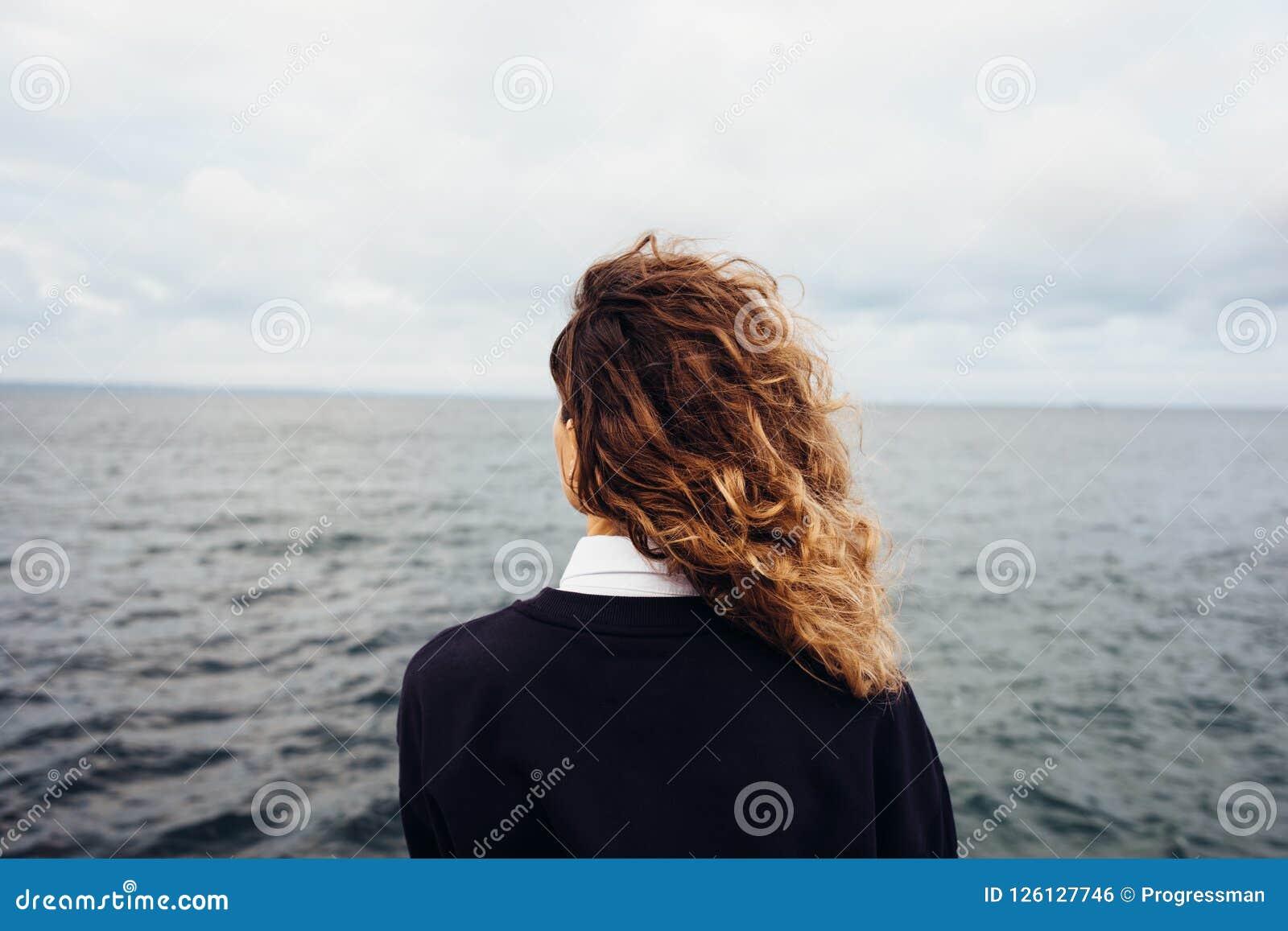 Tylni widok patrzeje chmurzącego nieba i szarość morze młoda kobieta