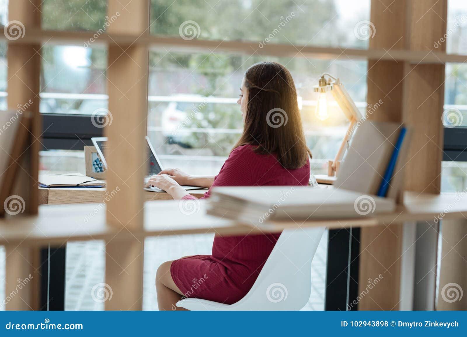 Tylni widok pracuje z laptopem młoda kobieta