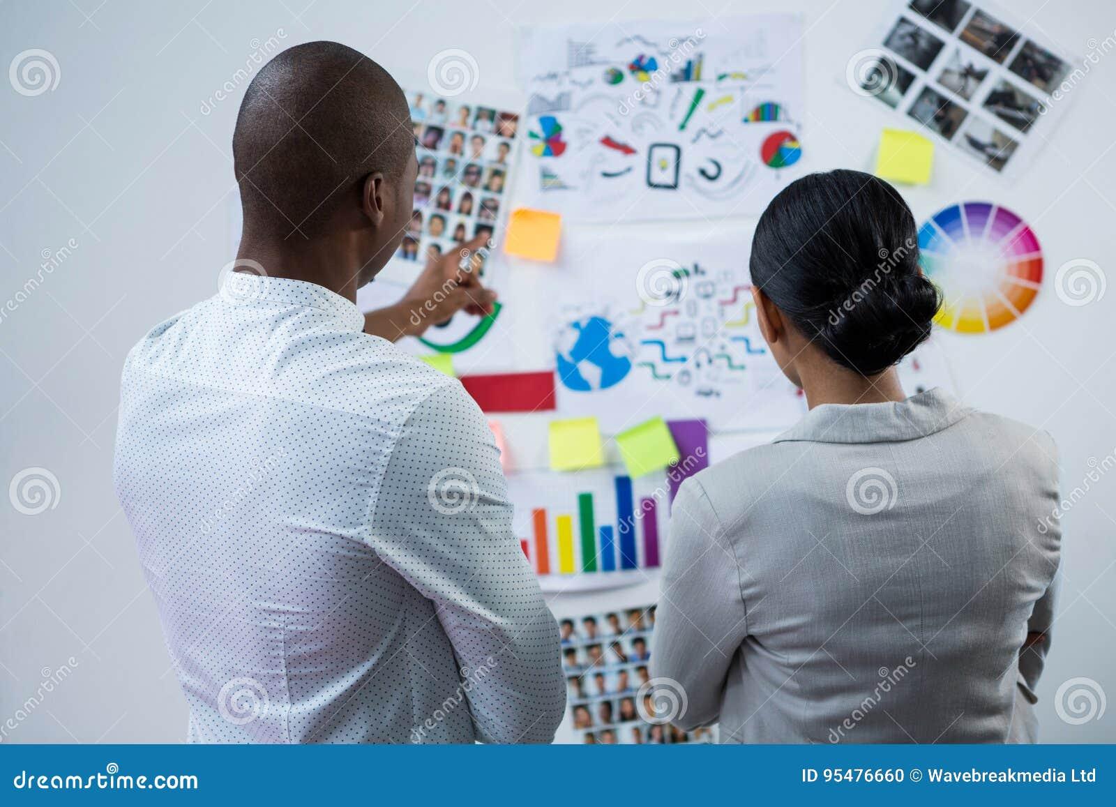 Tylni widok projektant grafik komputerowych dyskutuje nad mapami i wykresem