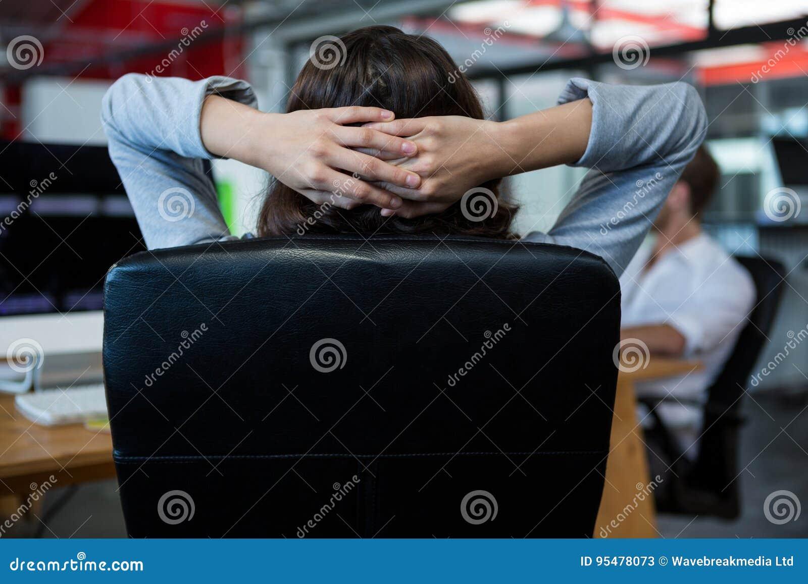 Tylni widok relaksuje na krześle bizneswoman