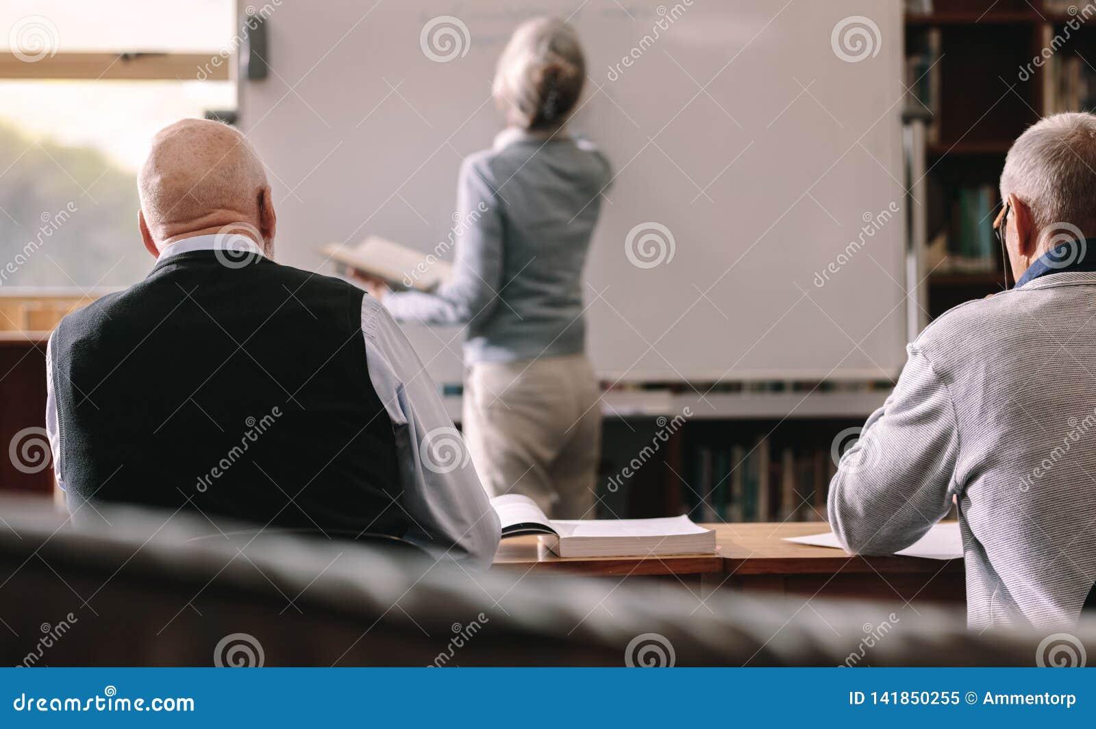 Tylni widok starszy mężczyźni siedzi w sali lekcyjnej