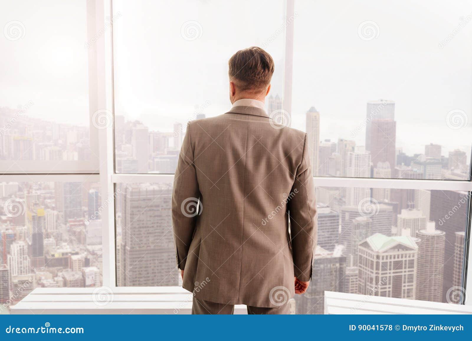Tylni widok stoi blisko okno biznesmen