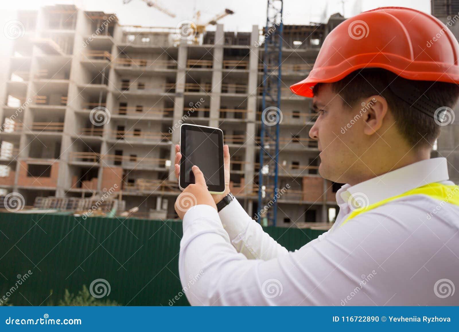 Tylni widoku wizerunek męski budynku pracownik używa cyfrową pastylkę na budowie
