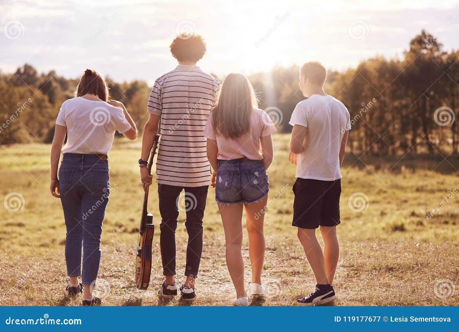 Tylny widok cztery przyjaciela przespacerowanie przez łąkę, trzyma gitarę akustyczną, przyjemną rozmowę, recreat podczas lato cza