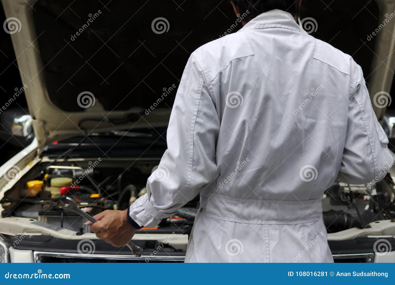 Tylny widok fachowy młody mechanika mężczyzna diagnozuje silnika przeciw samochodowi w otwartym kapiszonie przy naprawą w bielu m