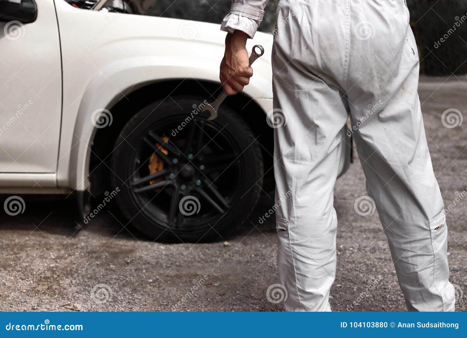 Tylny widok fachowy młody mechanika mężczyzna w jednolitym mienia wyrwaniu przeciw samochodowi w otwartym kapiszonie przy remonto