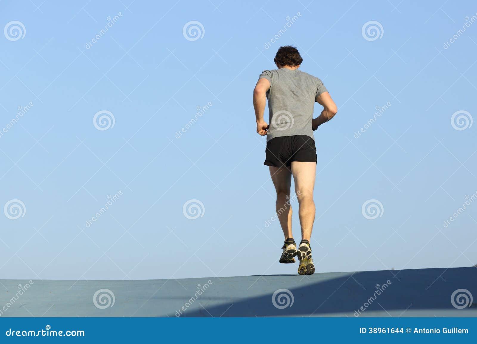 Tylny widok jogger mężczyzna bieg przeciw niebieskiemu niebu