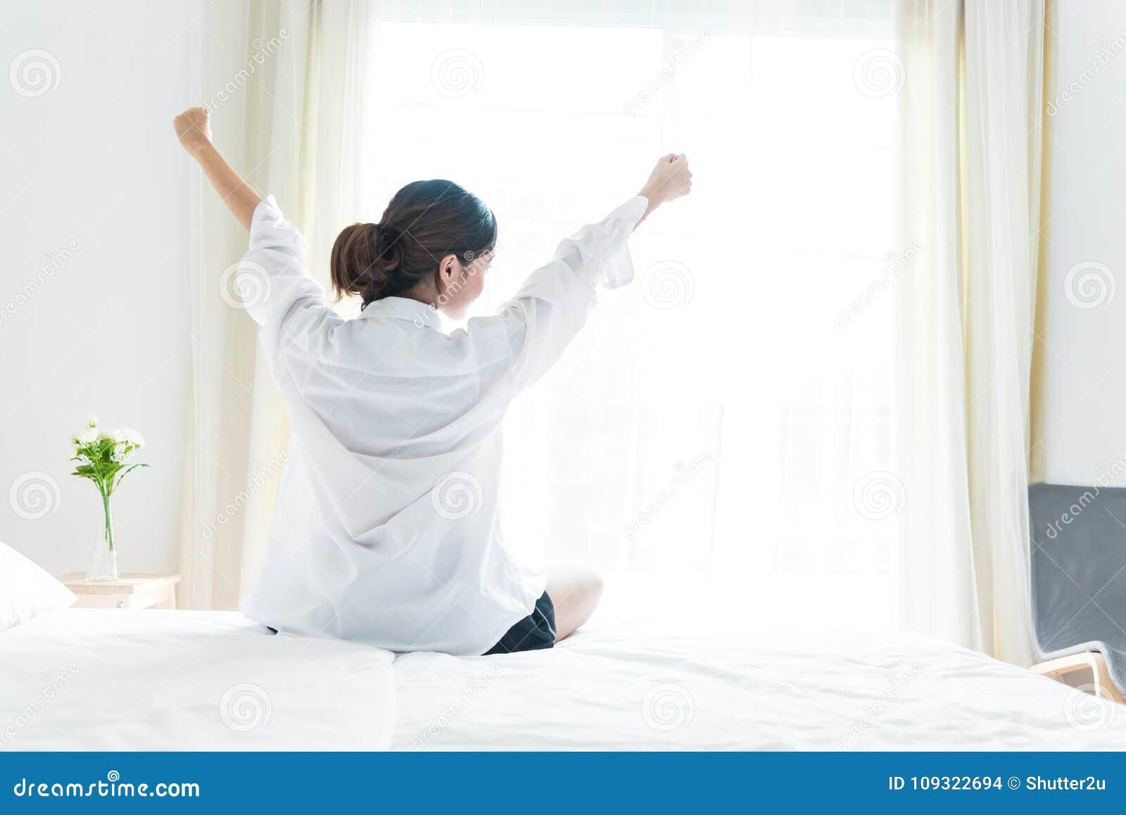 Tylny widok kobiety rozciąganie w ranku po budzić się up na łóżku