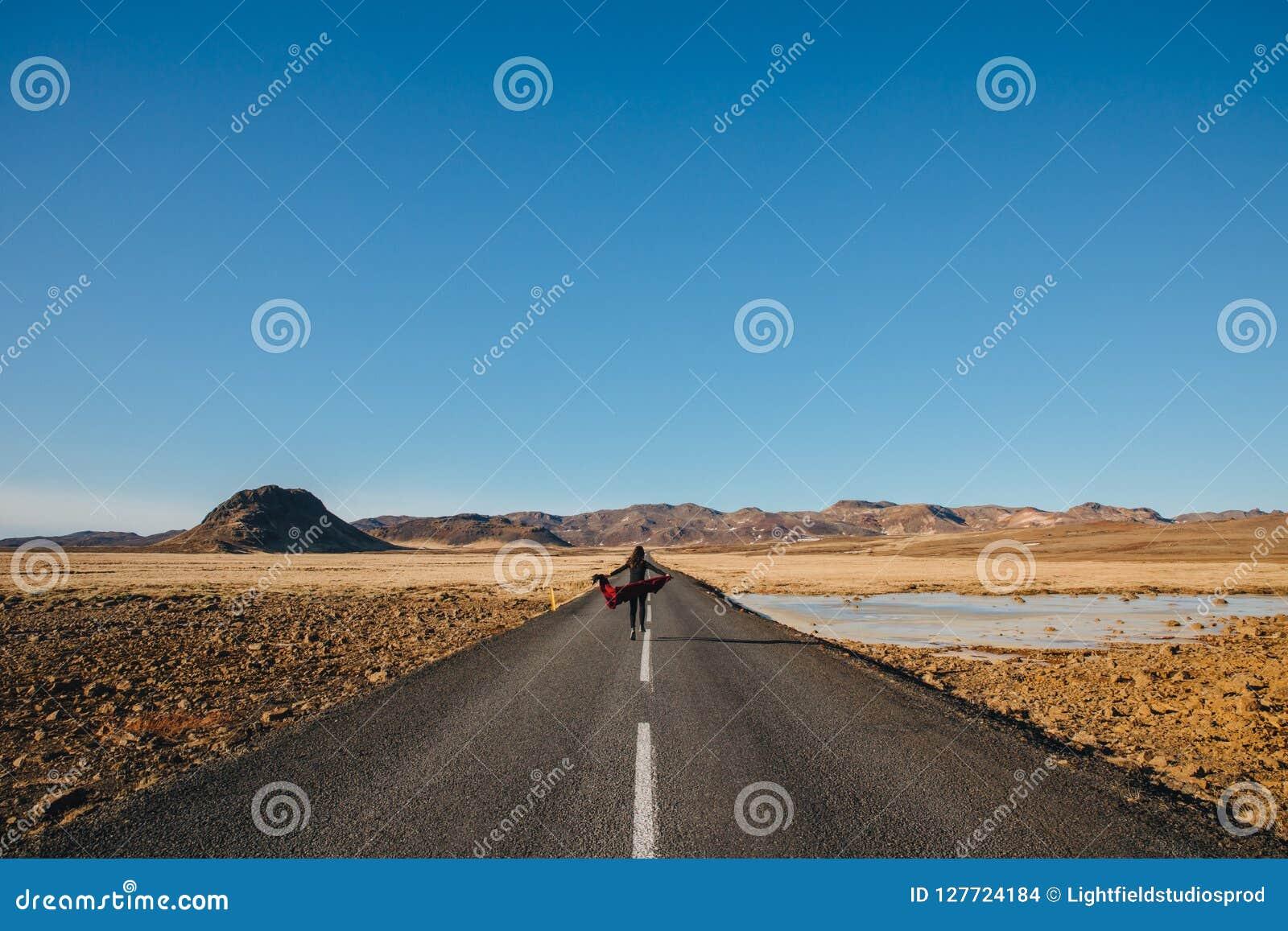 Tylny widok młodej kobiety odprowadzenie w asfaltowej drodze w Iceland, reykjanes