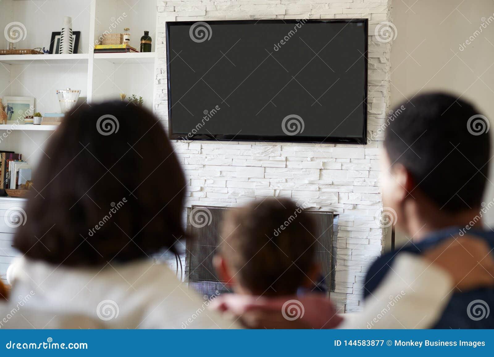 Tylny widok młody rodzinny obsiadanie na kanapie i dopatrywanie TV wpólnie w ich żywym pokoju, zakończenie w górę, ostrość na tel
