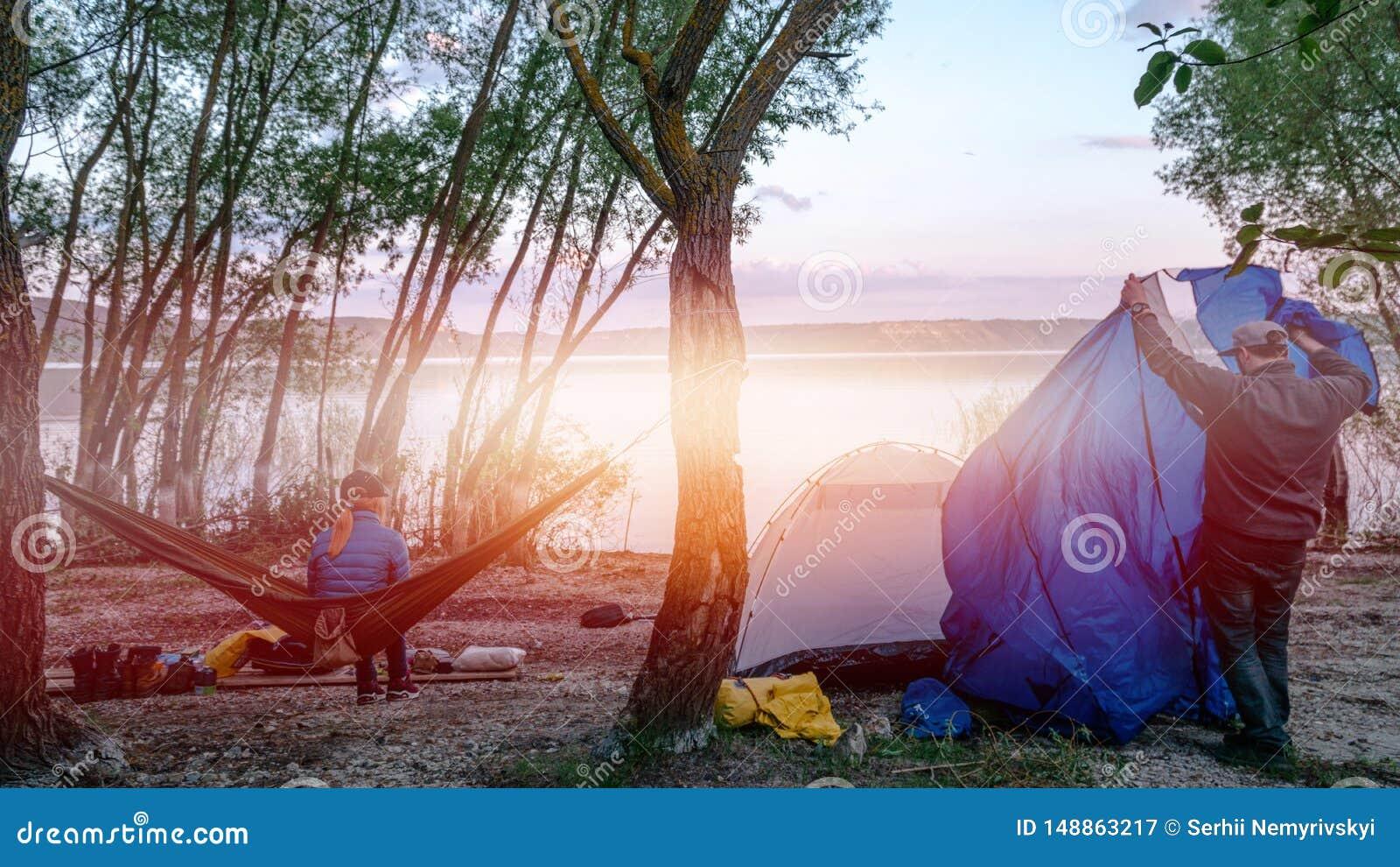 Tylny widok relaksuje na oliwnym hamaku mi?dzy dwa drzewami cieszy si? widok przy jeziorem w lato wiecz?r dziewczyna m??czyzna us