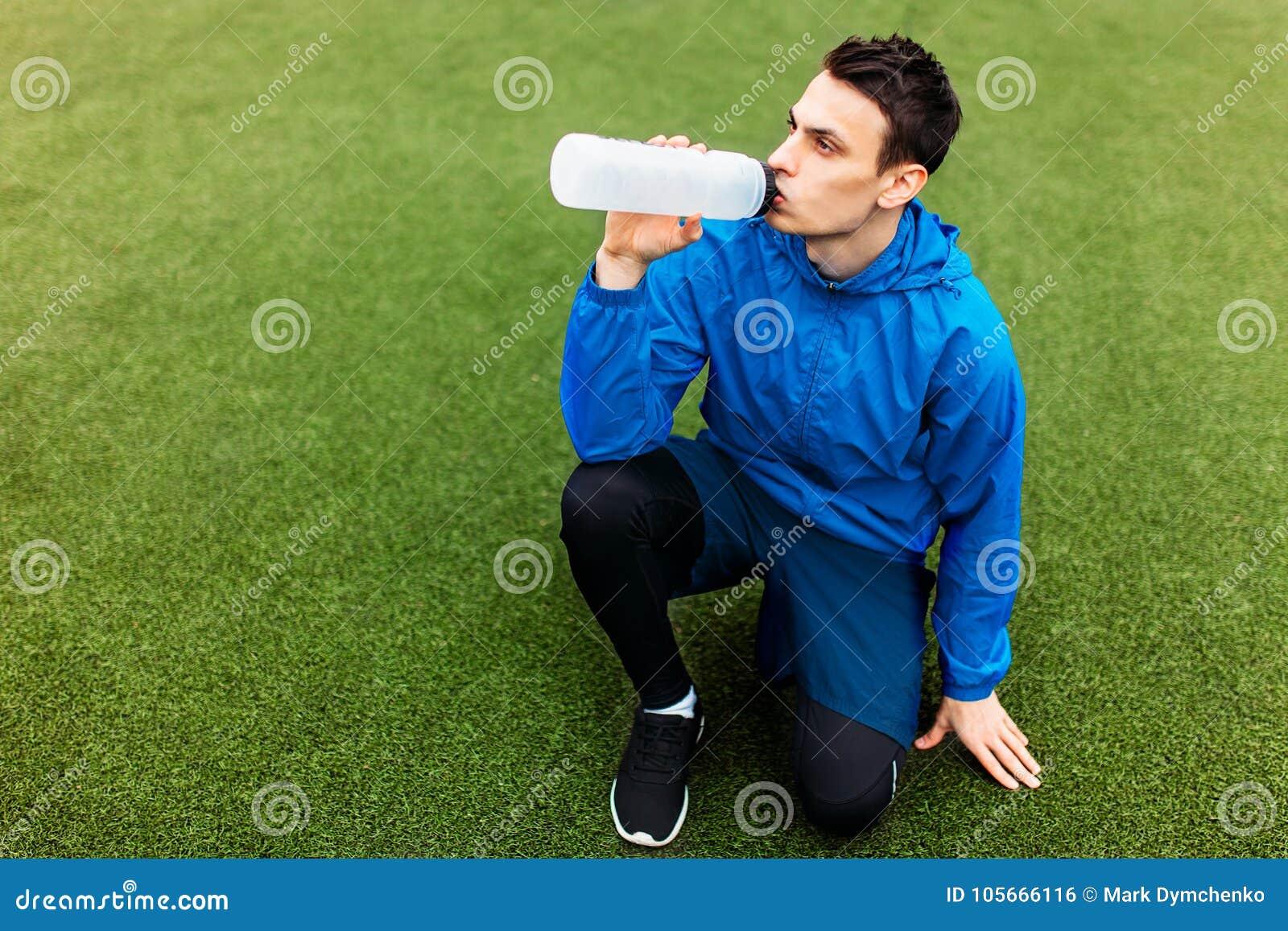 Type après exercice, eau potable sur le terrain de football Portrait de beau type dans les vêtements de sport