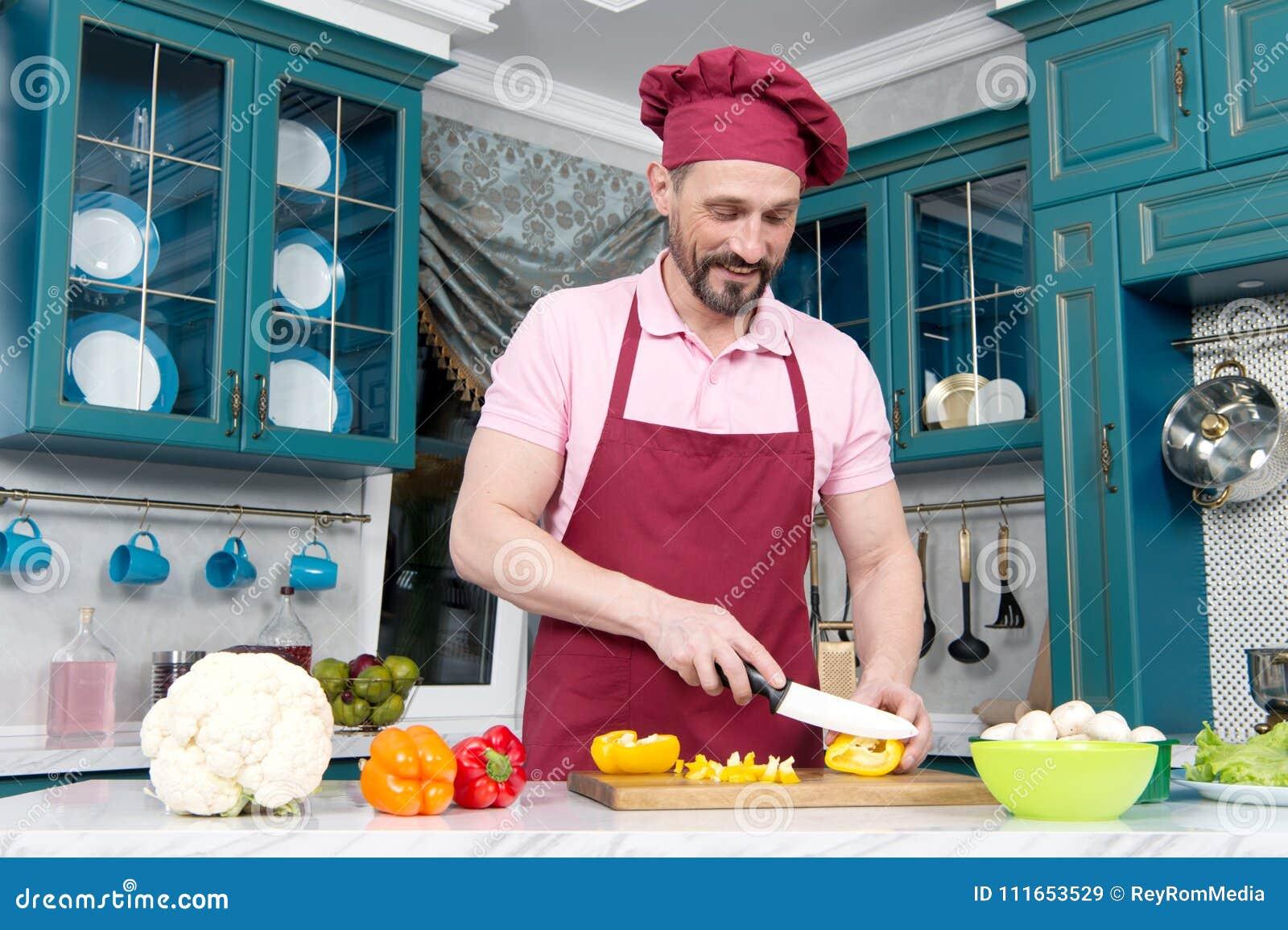 Type avec le couteau coupant le poivre orange sur la table Le cuisinier s est habillé dans le tablier préparent le dîner avec le