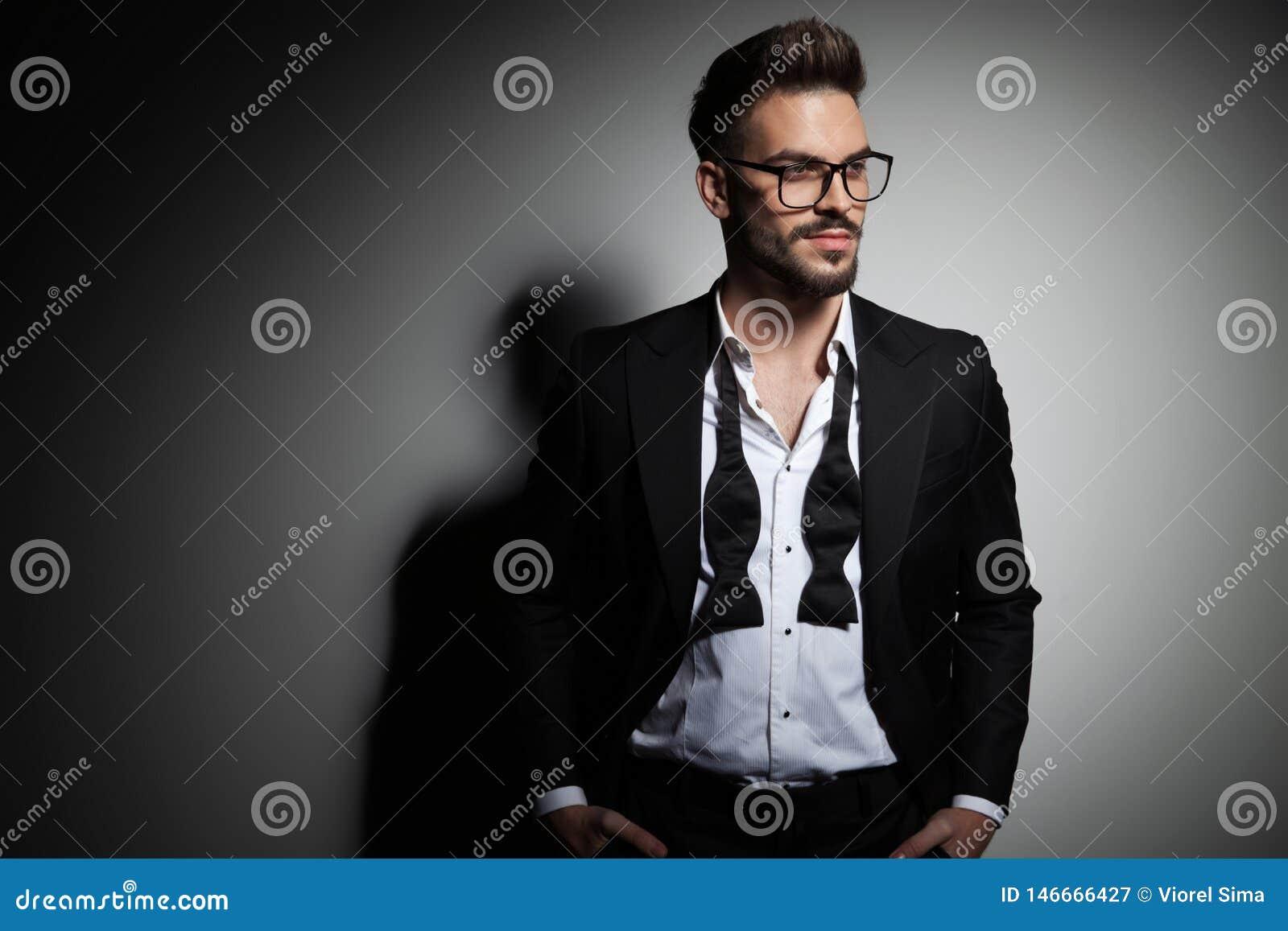 Type beau dans le smoking noir avec le collier défait regardant loin