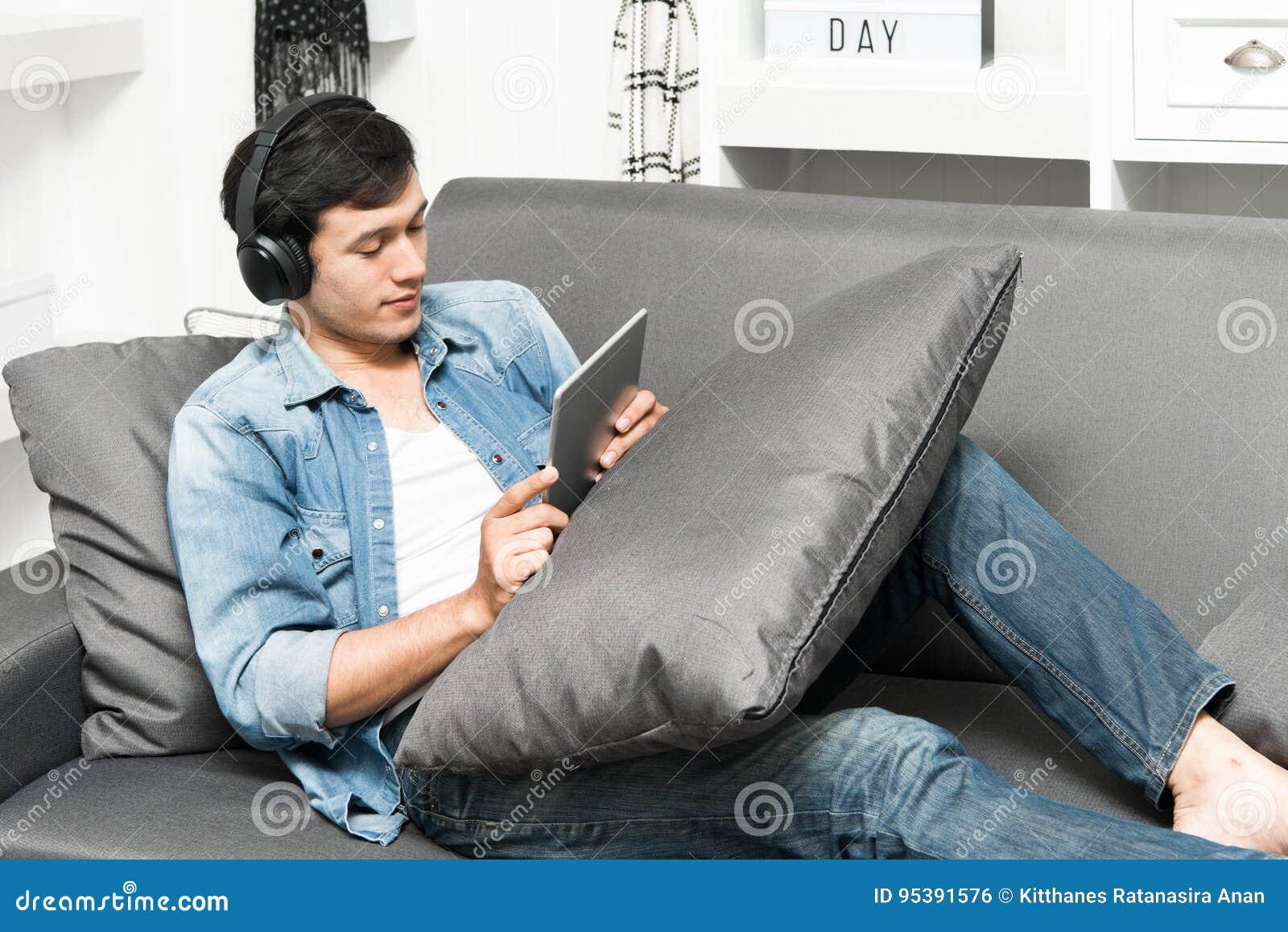 Type beau s asseyant sur le sofa avec des écouteurs