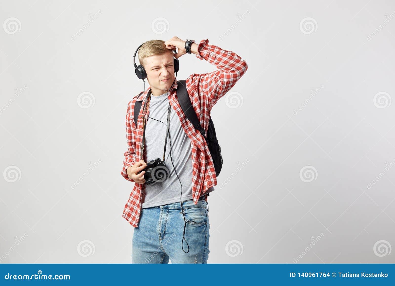 Type blond dans des écouteurs, avec le sac à dos noir sur son épaule habillée dans un T-shirt blanc, une chemise à carreaux rouge