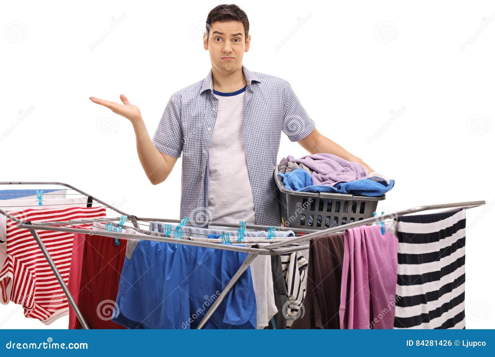 Type confus tenant le panier de blanchisserie derrière le dessiccateur de support d habillement