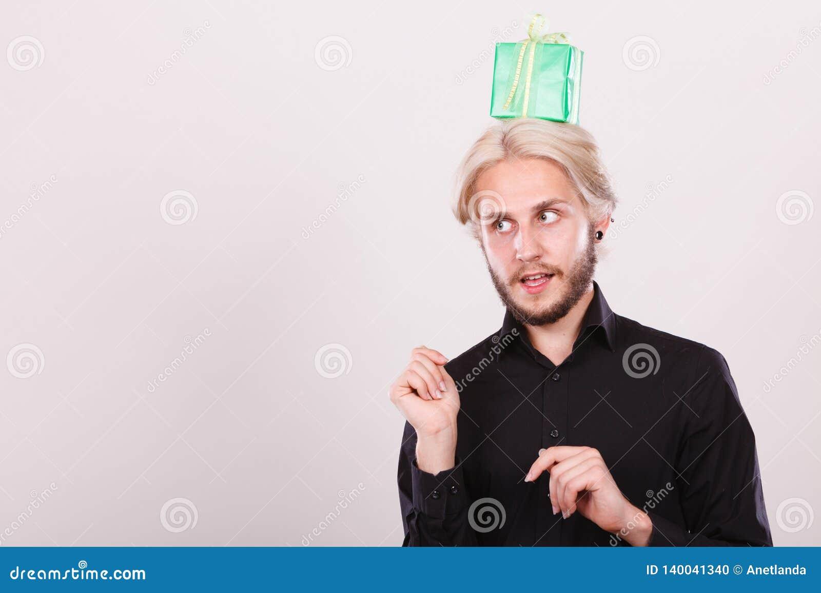Type de pensée avec le boîte-cadeau vert sur sa tête