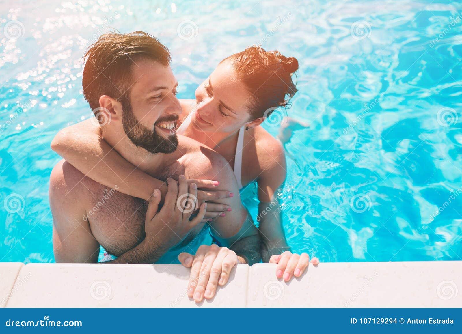 Type gai et dame jeunes se reposant tandis que piscine extérieure Couples dans l eau Les types font le sephi d été