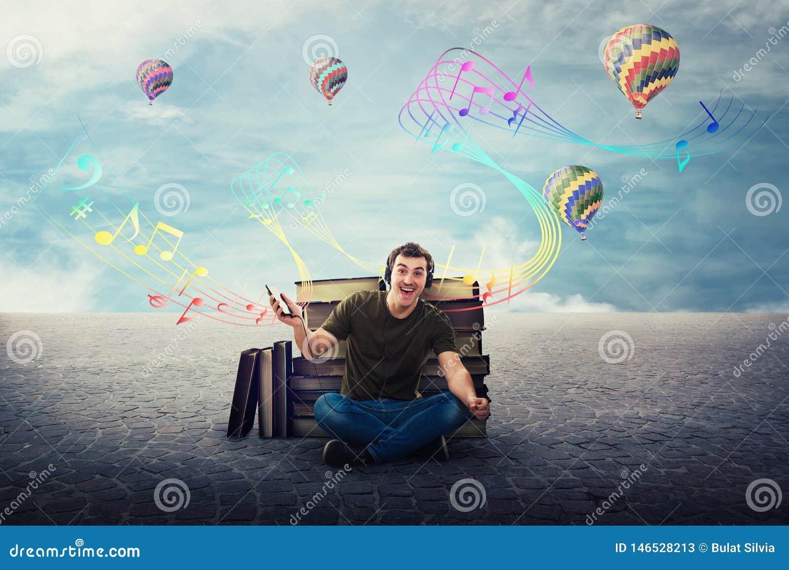 Type joyeux d étudiant assis détendu sur le plancher écoutant une chanson sur des écouteurs