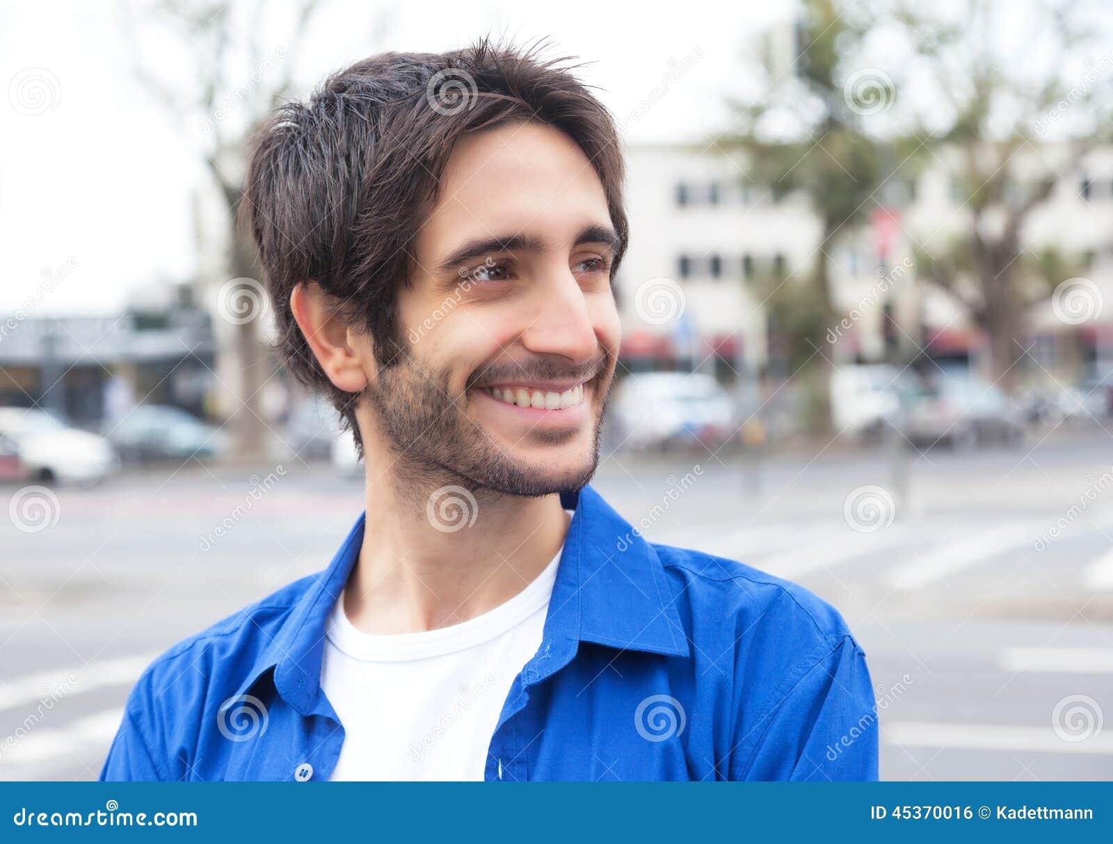 Type latin heureux dans une chemise bleue dans la ville