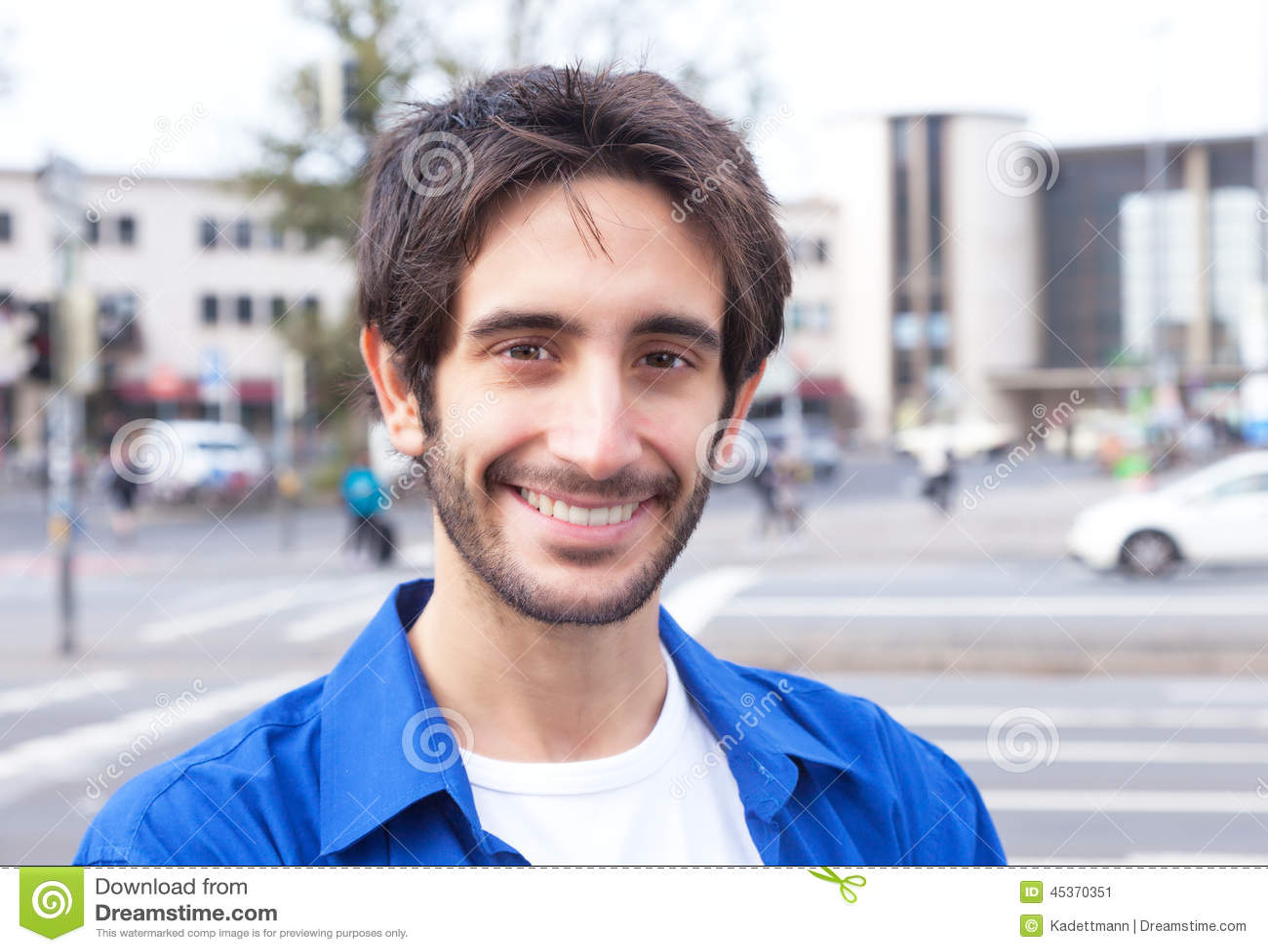 Type latin riant dans une chemise bleue dans la ville