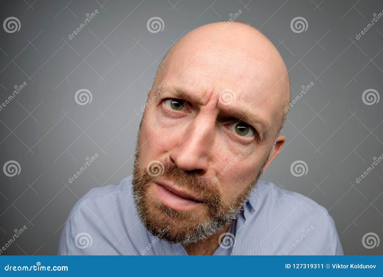 Type mûr chauve dans la chemise occasionnelle grise découvrant l appareil-photo caché
