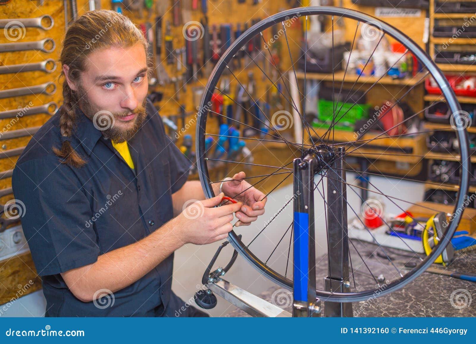 Type observé bleu réparant la bicyclette dans l atelier