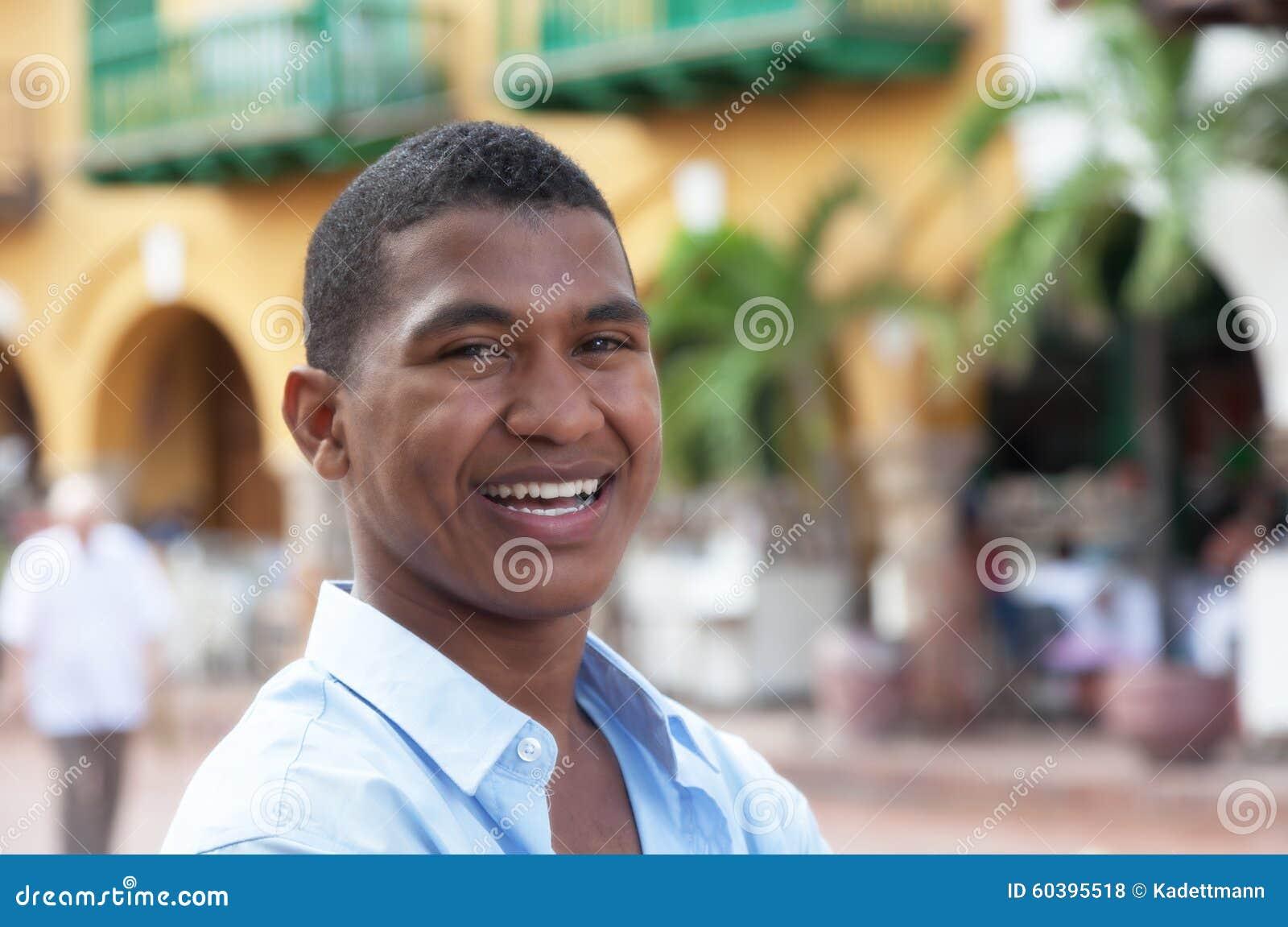 Type riant dans une chemise bleue dans une ville coloniale colorée