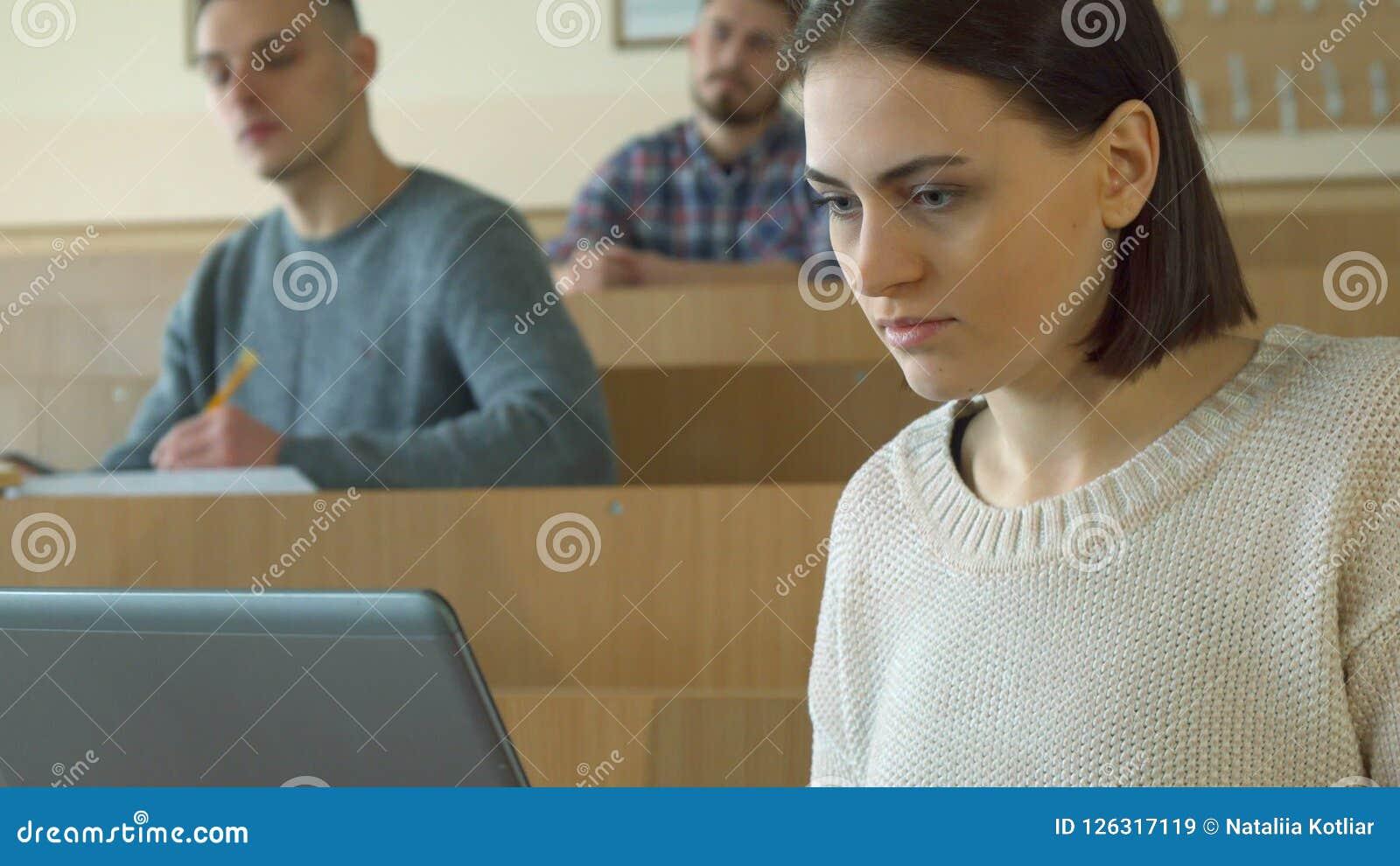 Typer för kvinnlig student på bärbara datorn