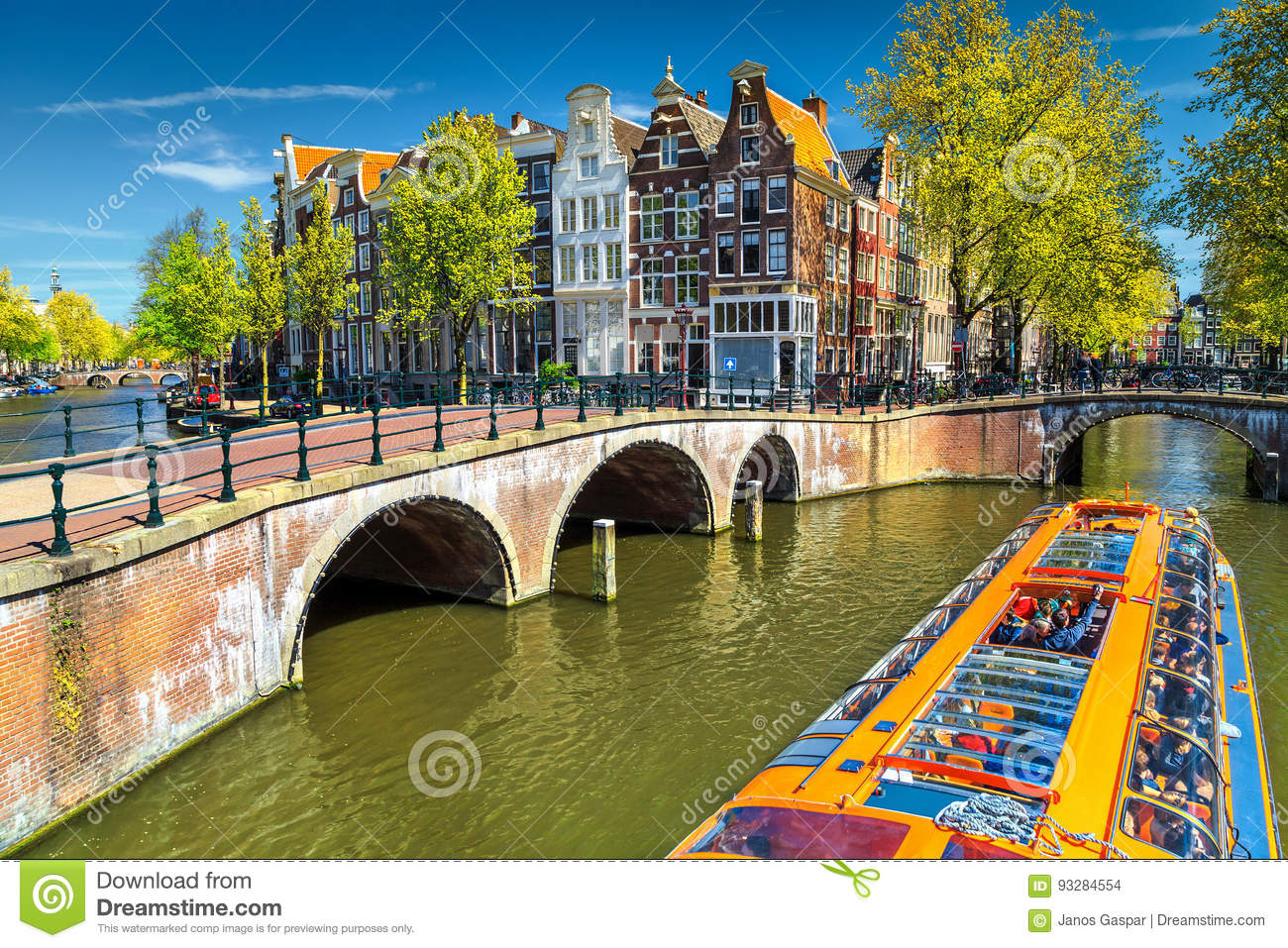 Typical Amsterdam canals with bridges and colorful boat, Netherlands, Europe