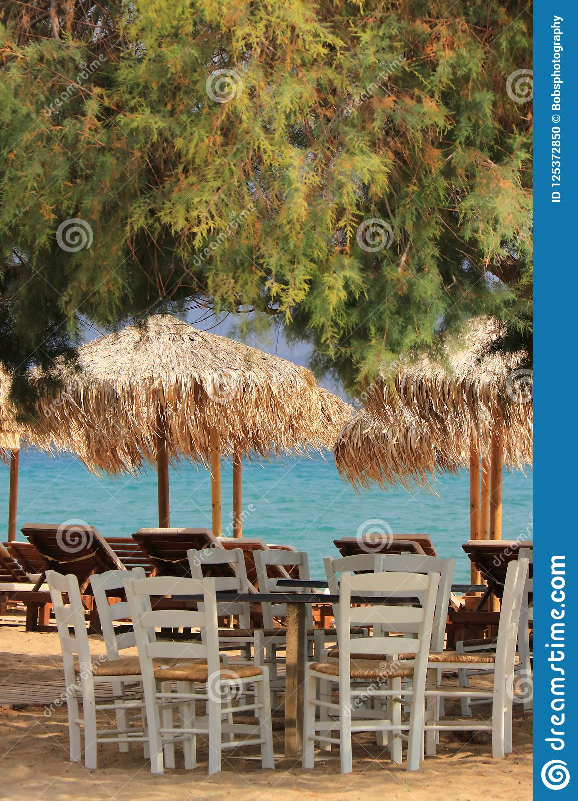 Typical greek scene at the kalives beach with wooden chairs and table